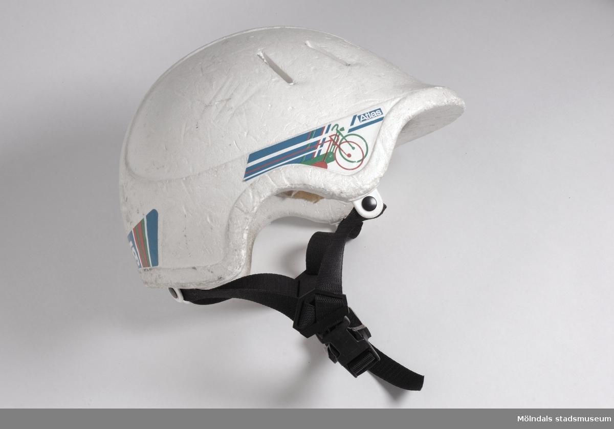 """Vit frigolithjälm med svarta remmar runt hakan.Ägaren/givaren köpte hjälmen efter att ha krockat med annan cyklist. Har brutit nyckelben, fraktur på kindben, 2 stygn i ögonbryn och 1 stygn i örat.Text på insidan av hjälmen: """"Utformad enligt konsumentverkets regler för säkerhet och funktion för cykelhjälmar"""""""