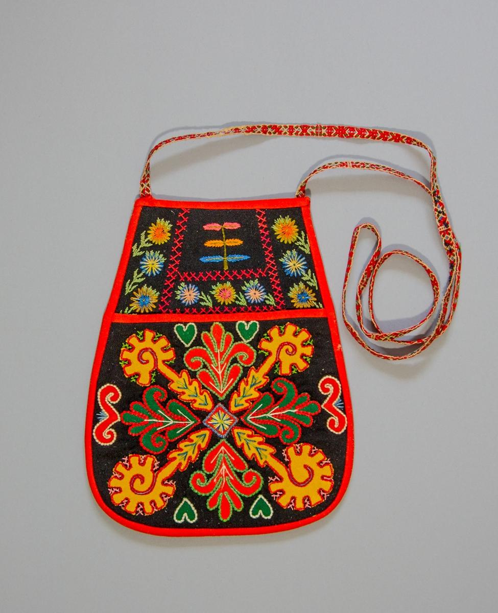 Kjolsäck till dräkt för kvinna från Gagnefs socken, Dalarna. Modell med avskuret framstycke. Tillverkad av svart ylletyg, kläde, med applikationer av kläde i gult, grönt och rött. Motiv med korsvis ställda förlängda hjul och samt bladformer, omgivna av slingor och små hjärtan. Broderad med ull- och bomullsgarn i många färger: läggsöm, flätsöm, sticksöm och plattsöm, även på överstycket. Foder av fabriksvävt bomullstyg i blått och vitt, s.k. systertyg. Kantad runtom med remsor av rött kläde. Baksida av fabriksvävt bomullstyg, med ränder i flera färger på mörkblå botten. Midjeband handvävt, med plockat mönster av ullgarn i rött, grönt och ljusblått på botten av lingarn.