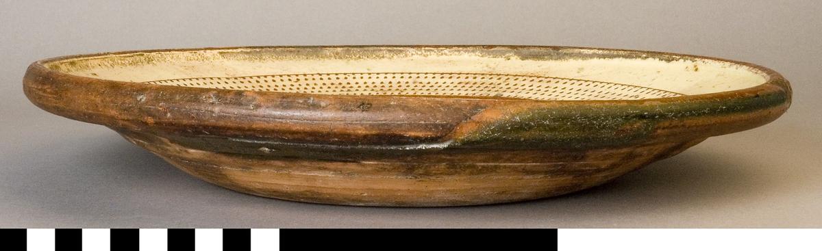 Fat av lergods med målad dekor på engobe av piplera. Runt fatets bräm finns bård med skraffering. Runt om en slinga dekorerad med girlanger. Kring spegel stiliserad blad i en bård I spegel årtalet 1746. Glaserat.