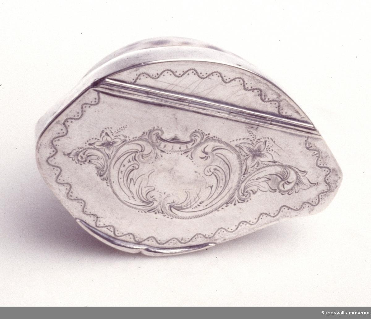 Snusdosa tillverkad av en porslinssnäcka med silverlock och fattning. Locket är förgyllt invändigt. På locket finns graverad dekor föreställande blommor och en kartusch i nyrokoko-stil. Stplr: C.W. Edwall, Sundsvall 1879.