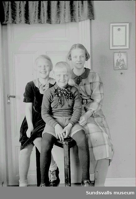 Grupporträtt. Tre syskon i rumsmiljö.