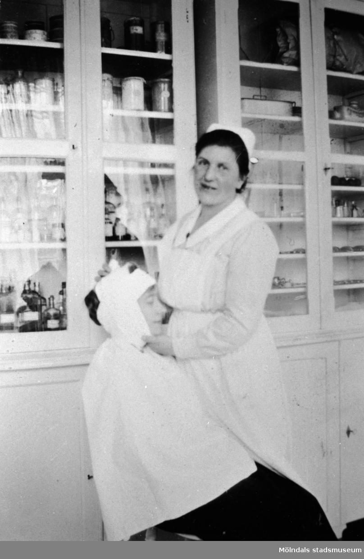 En sköterska bandagerar en patients huvud, i medicinrummet på Stretereds skolhem, 1926.