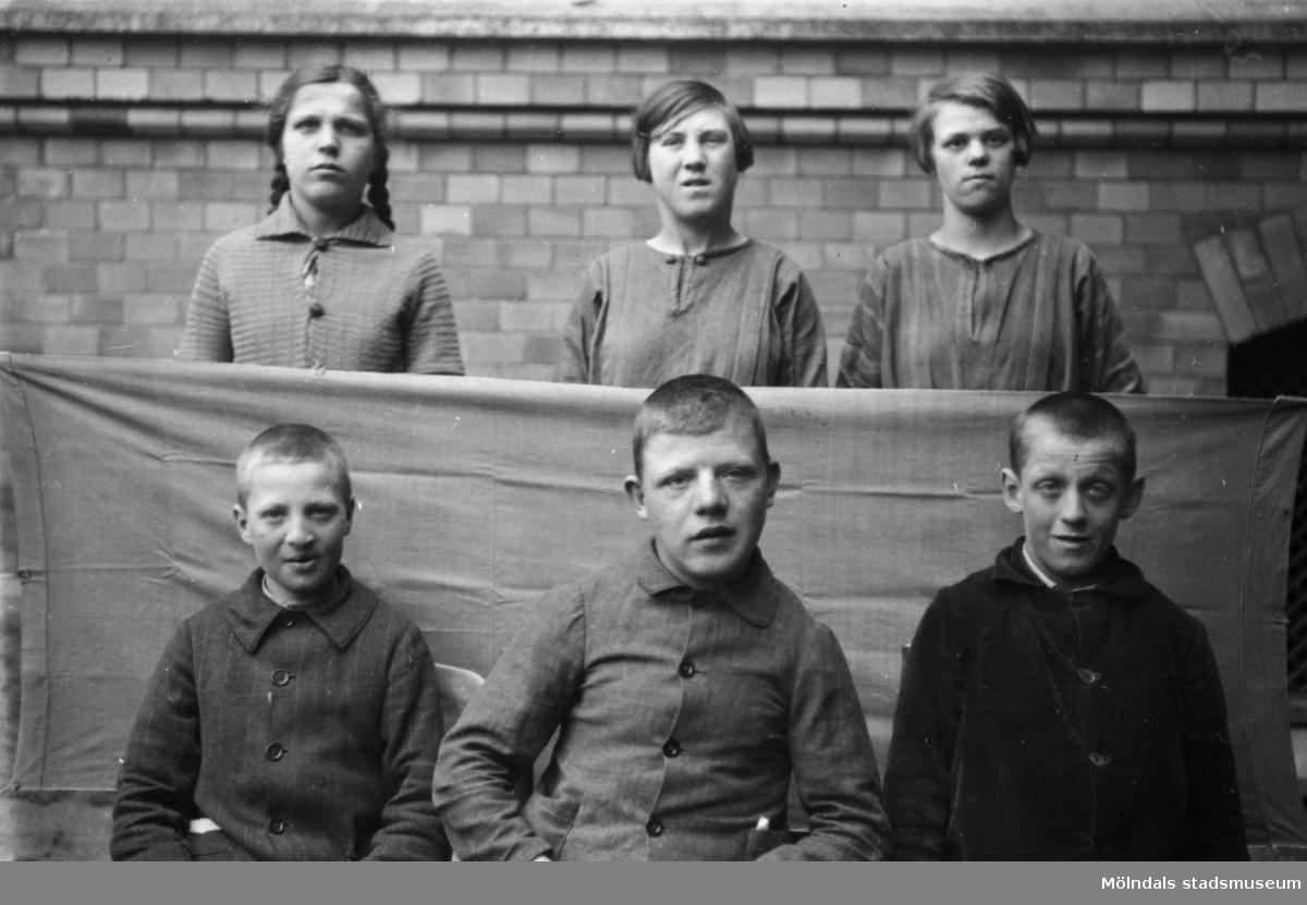 Pojkar och flickor framför en vägg utanför Stora skolan på Strereds skolhem.