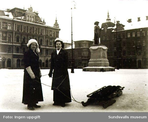 Två kvinnor med kälke på Stora torget i Sundsvall. I bakgrunden syns Harald Sörensen-Ringis staty av Gustav II Adolf, rest 1911.
