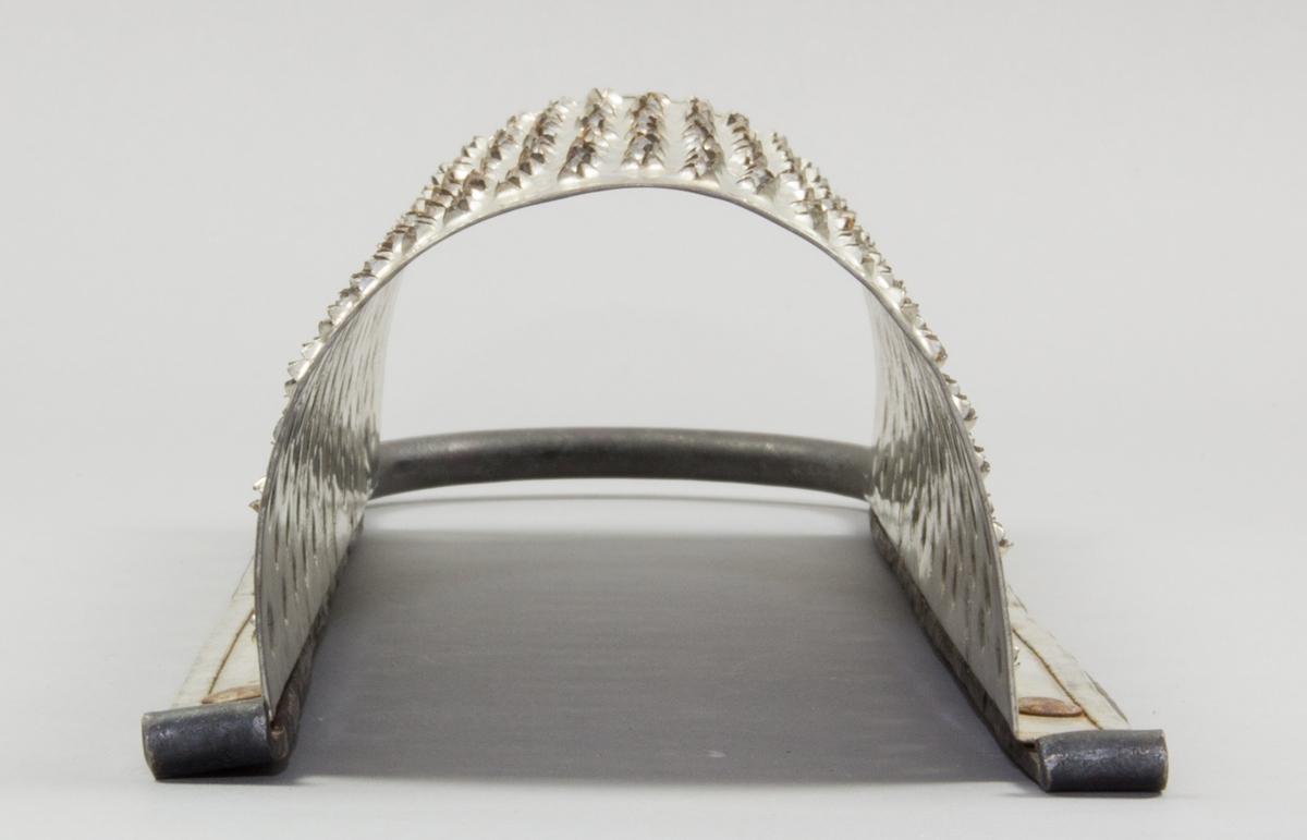 Rivjärn tillverkat av järn. Den perforerade plåten är fogad till en båge som bildar ett valv.. Plåten  i valvet är perforerad med spik. Upptill finns ett bågformat handtag.