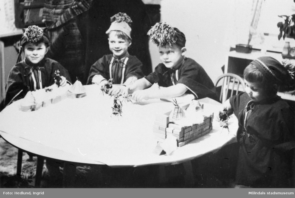 Bosgårdens barnträdgård 1938-1945. Barn som sitter vid ett bord utklädda till samer. Barnen har tillverkat sina egna enkla samekläder och mössor, med bl.a pärlträdning i lappfärger osv. Deras förskollärare Ingrid Hedlund hade gjort sitt examensarbete om samehantverk och denna kunskap använde hon i sitt pedagogiska arbete under flera år.