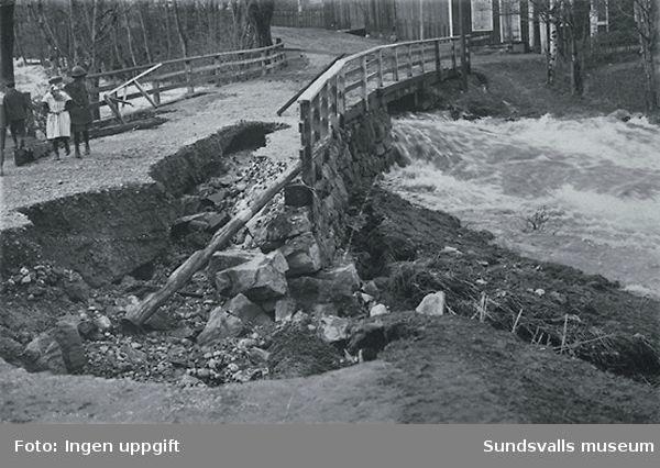 Gamla bron över Sidsjöbäcken uppe vid Fagerdal i närheten av fröknarna Löfgrens speceriaffär. Kortet taget vid översvämningen 1919.  På bild tre barn.