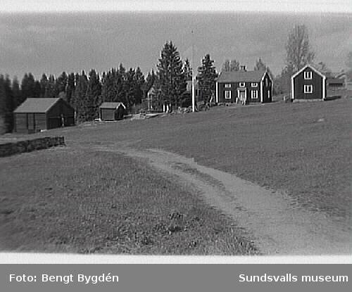 Nya och gamla kyrkan på Alnö, kyrkskolan, hembygdsgården samt intilliggande bebyggelse.