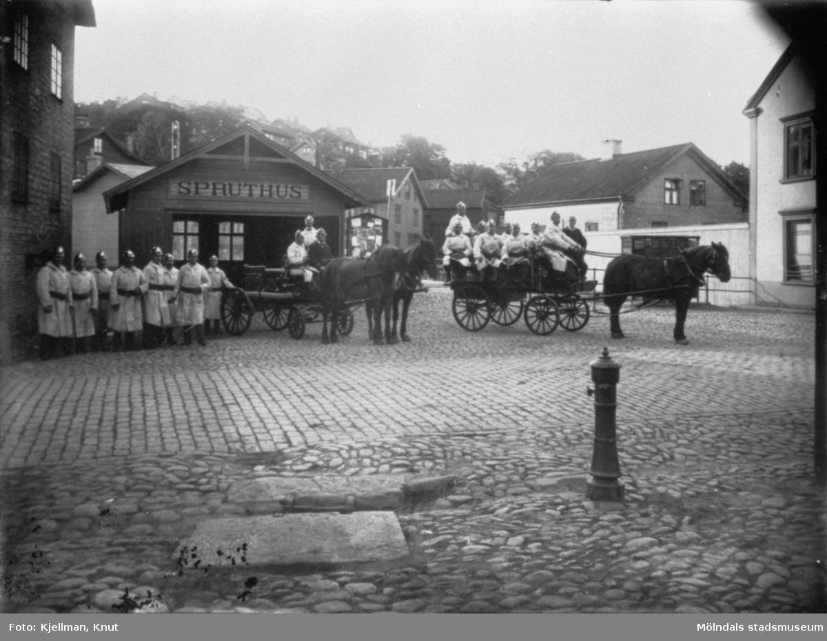 Brandkåren står uppställda framför Spruthuset, mittemot Gamla torget i Mölndals kvarnby år 1915. Männen står till fots samt sitter på hästdragna vagnar. Spruthuset var en slags brandstation och användes t.o.m 1935 då nya brandstationens hus på Kvarnbygatan 41 togs i bruk. Till höger ser man ett par fönster på Byggnad 213.