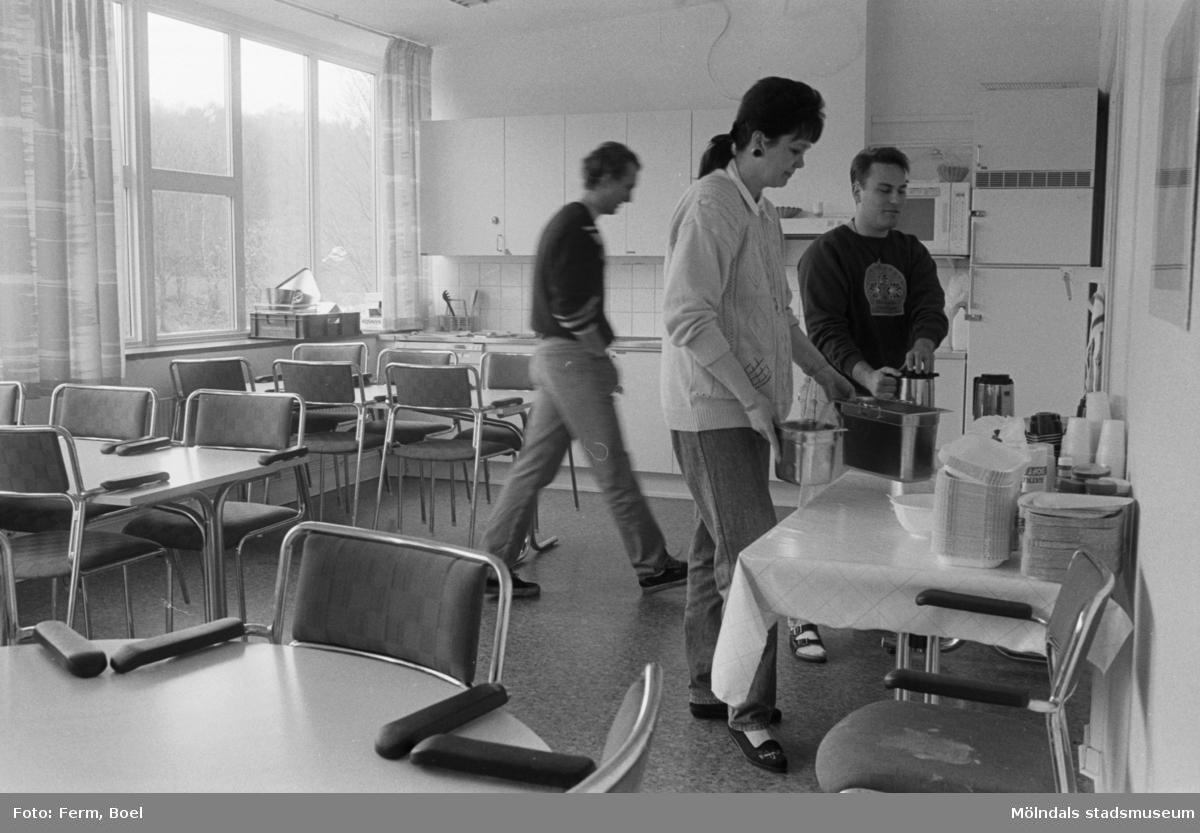 Dokumentation av Sagåsens flyktingförläggning 1992. En kvinna och två män i ett kök, där de tar mat från kantiner.