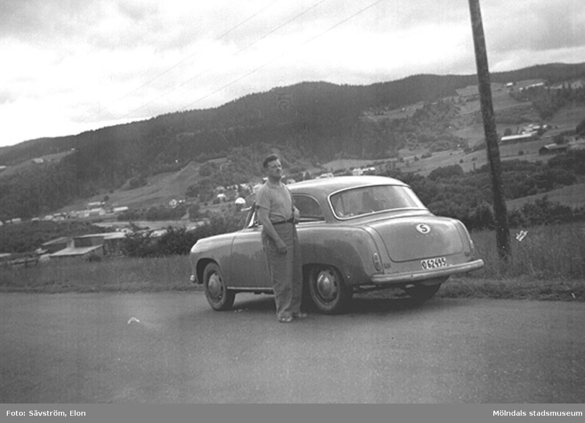 Helmer Garthman är på väg till Norge för fiskesemester med Elon Sävström och dennes bil, en Goliat Isabella. Här är det paus i Värmland. 1960-tal. Skänkt av sonen Alf Garthman som arbetade många år på Mölndals stadsmuseum.