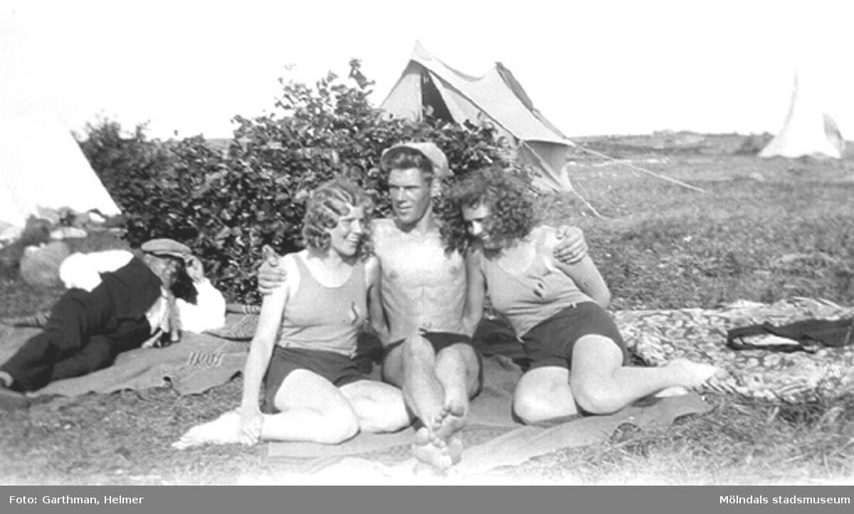 Helmer Garthmans kompisar, från vänster: Anna Nilsson, Wilgot och Gitt Ullberg. De sitter på en filt framför en buske vid sjön Lygnern i Fjärås. Okänd man i bakgrunden. 1930-tal.
