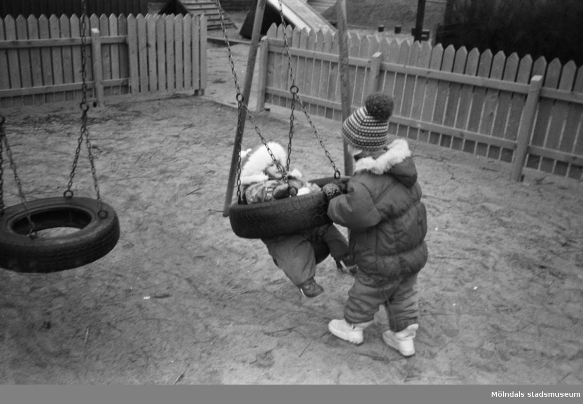 Ett cirka 4-årigt barn gungar ett mindre barn som sitter i en barngunga bestående av däck. De är på lekplatsen med sand utanför Katrinebergs daghem.