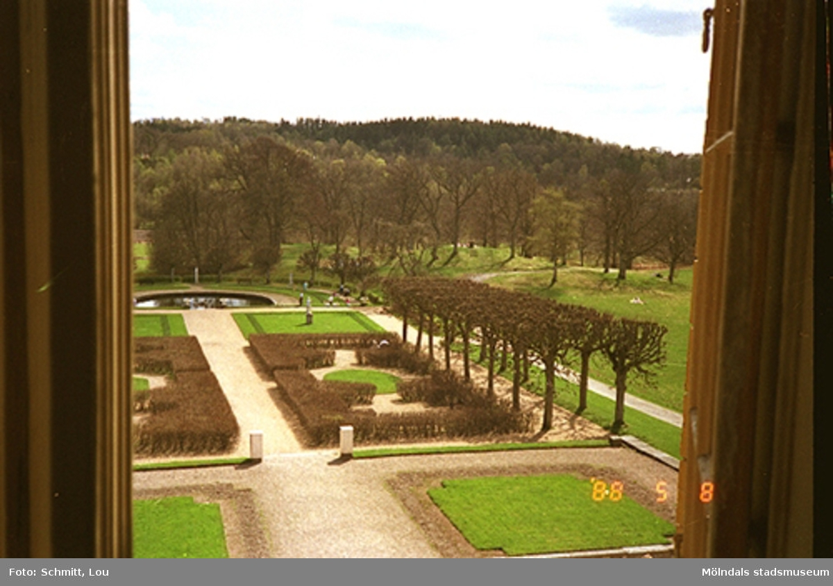 En del av parken på Gunnebo slotts högra baksida. Bilden är tagen inifrån och ut genom ett öppet brunt fönster. I bakgrunden skymtar man dammen.