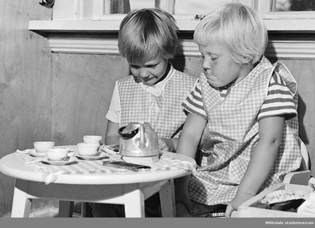 """Två flickor sitter vid ett barnbord och """"dricker kaffe"""". Holtermanska daghemmet 1953."""