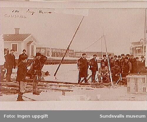 """Bärgning av båt i Sundsvalls hamn, med dykarlag sittande t.h. T.v. i bakgrunden den gamla lotsstugan på norra sidan av Selångersåns mynning. T.h. skymtar aktern på passagerarfartyget """"Tynderö""""."""