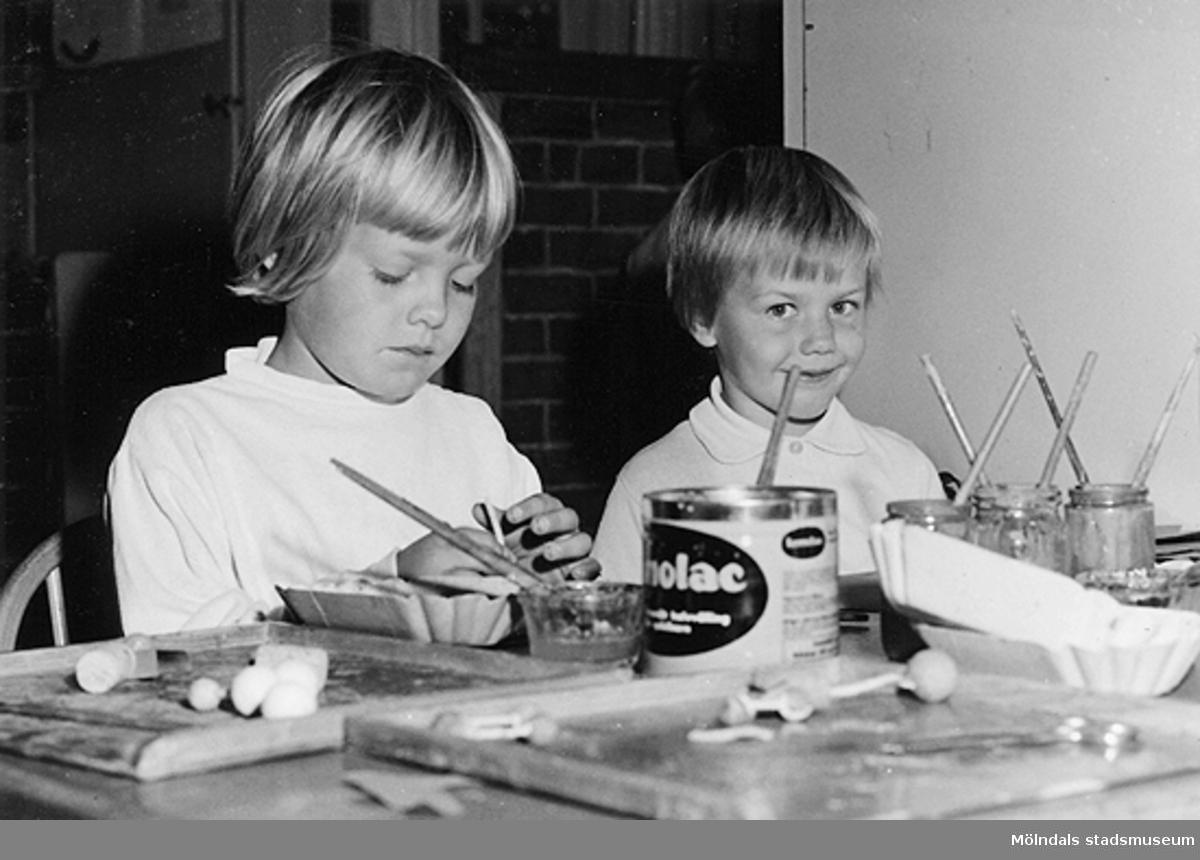 Två barn målar och pysslar vid ett bord. Holtermanska daghemmet 1953.