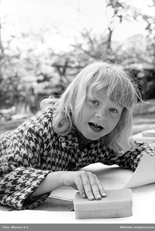 En flicka som håller en svamp och ett papper i händerna. Holtermanska daghemmet juni 1973.