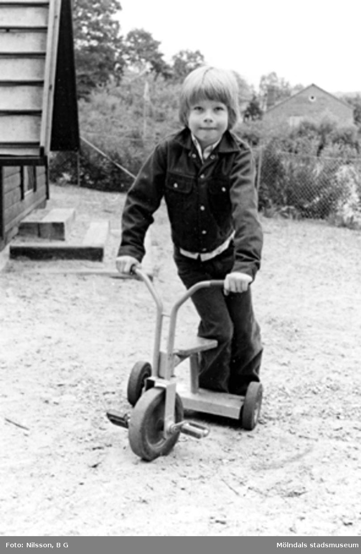 En pojke står på en trehjuling. Holtermanska daghemmet 1973.