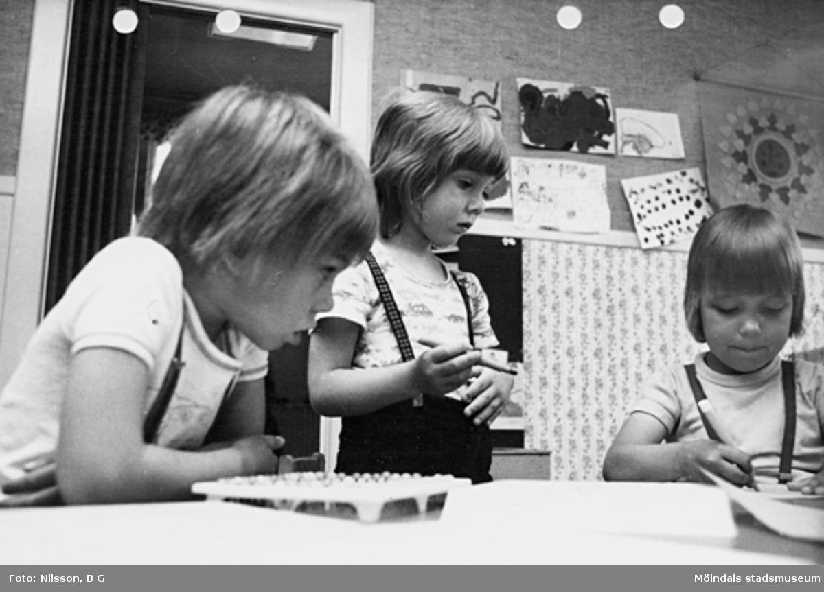 Två barn som ritar och ett barn tittar på. Holtermanska daghemmet maj 1975.