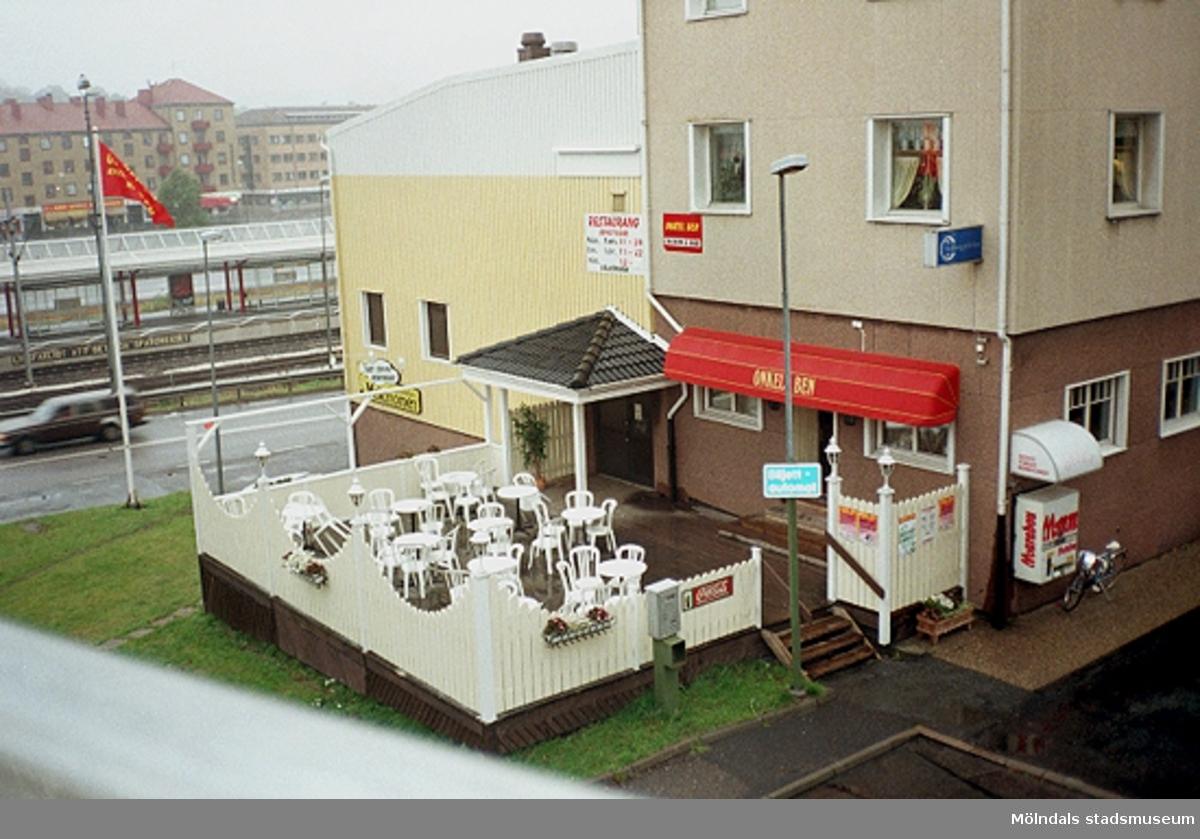Butik och restaurang på Nämndemansgatan 1, östra sidan av järnvägen. Mölndalsbro i dag - ett skolpedagogiskt dokumentationsprojekt på Mölndals museum under oktober 1996. 1996_1212-1226 är gjorda av högstadieelever från Kvarnbyskolan 9D, grupp 5. Se även 1996_0913-0940.