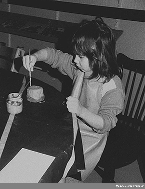 Okänt barn målar på ett föremål. Elsa Sahlqvist var på besök och hjälpte barnen att arbeta med keramik i januari 1985. Hon ordnade också en uttällning med barnens keramikarbeten. Kulf (Kulturen i förskolan) anlitade Elsa för att stödja kulturarbetare.