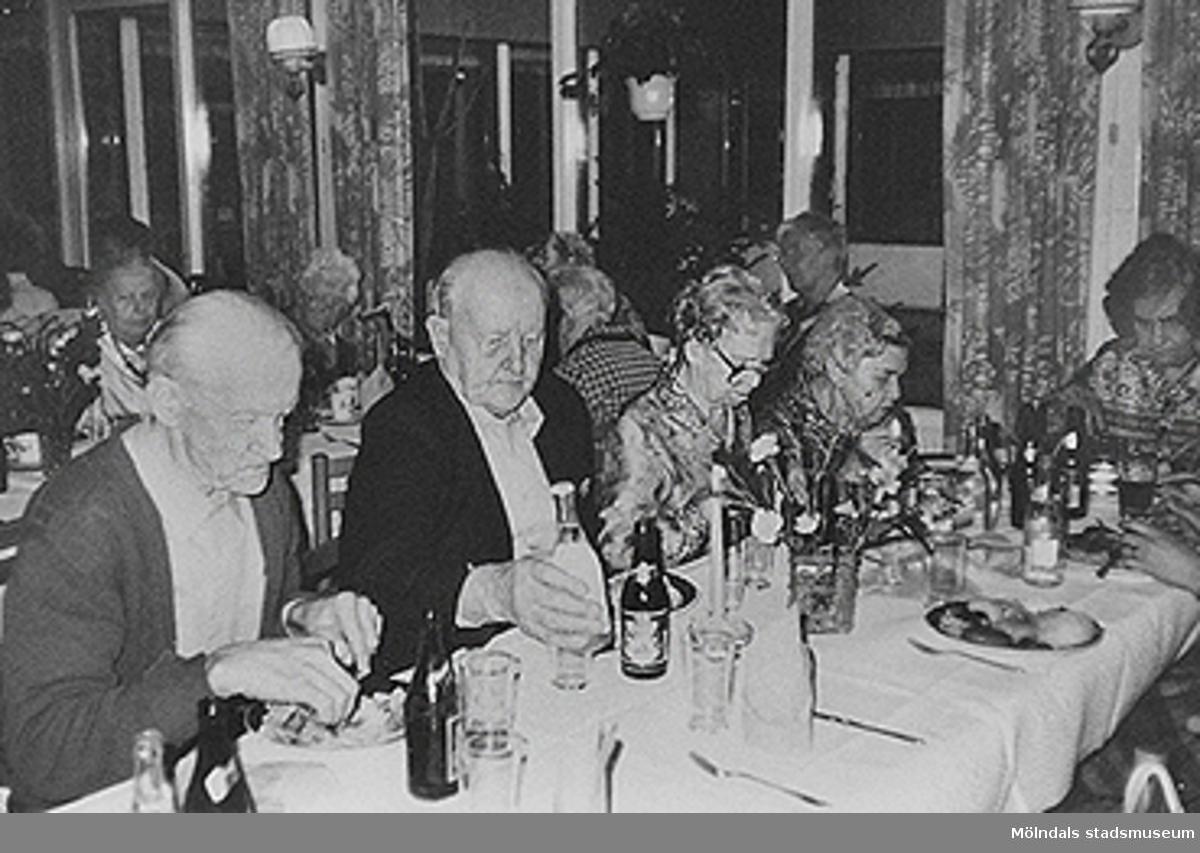 Mat och dryck står på borden och de boende äter utav detta. Okänt årtal.
