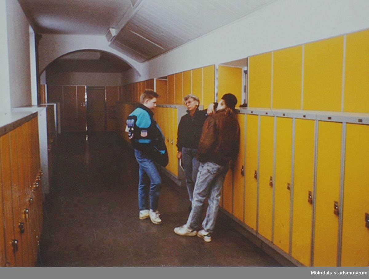 En lärare pratar med två elever i en korridor. Okända.