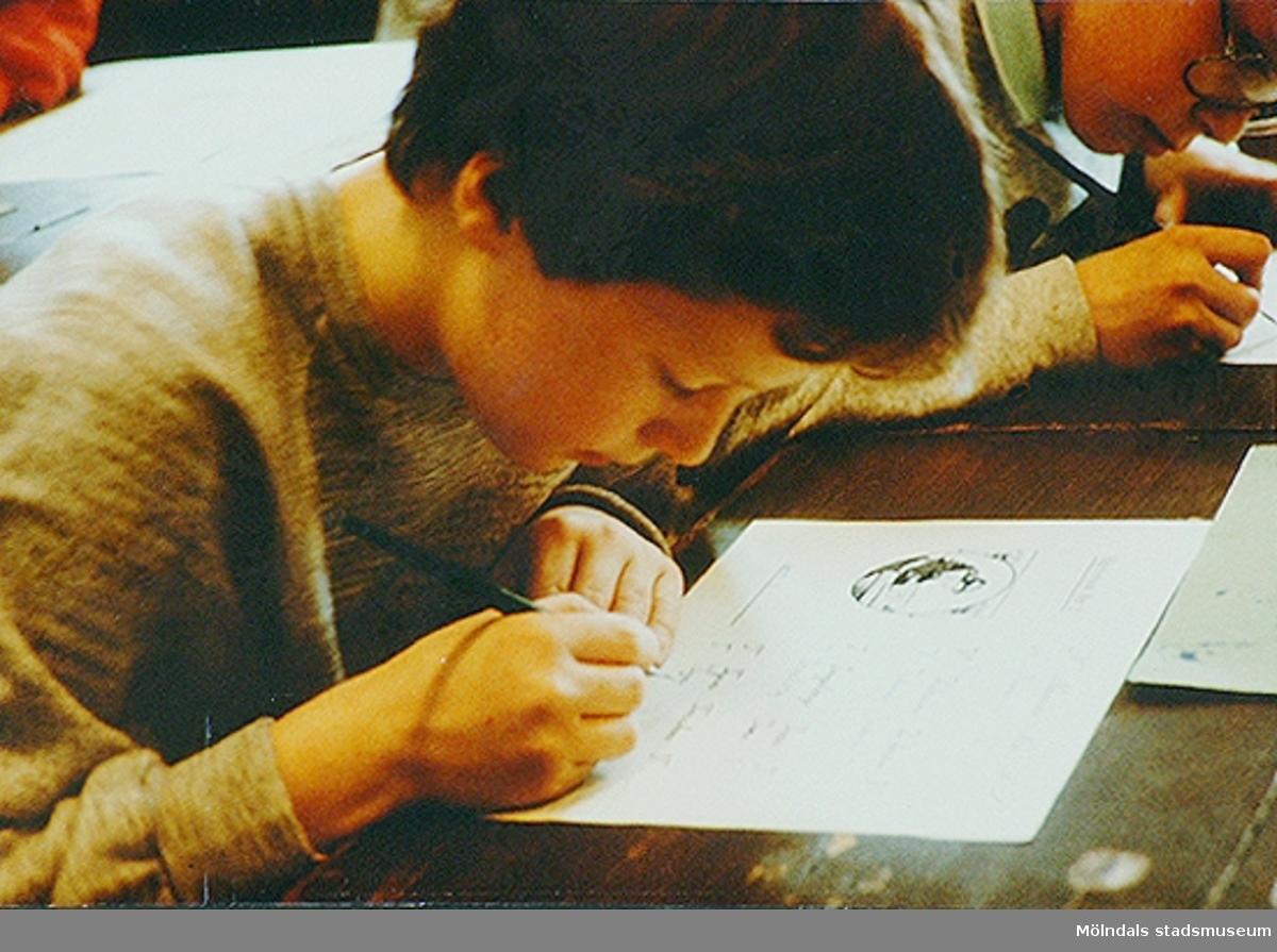 Ett barn som sitter vid en bänk och skriver finstil med bläckpenna. Okänt årtal.