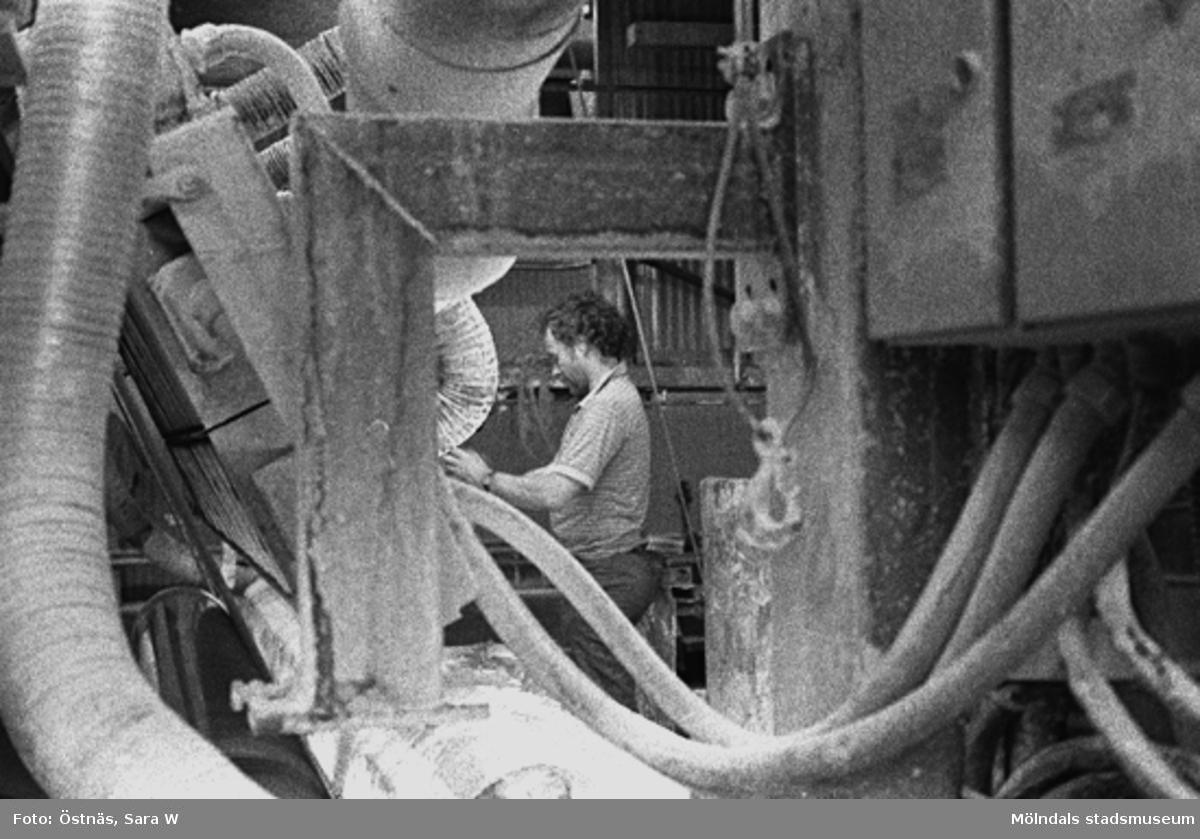 En man i arbete. Juris Kuvalds.Bilden ingår i serie från produktion och interiör på pappersindustrin Papyrus.