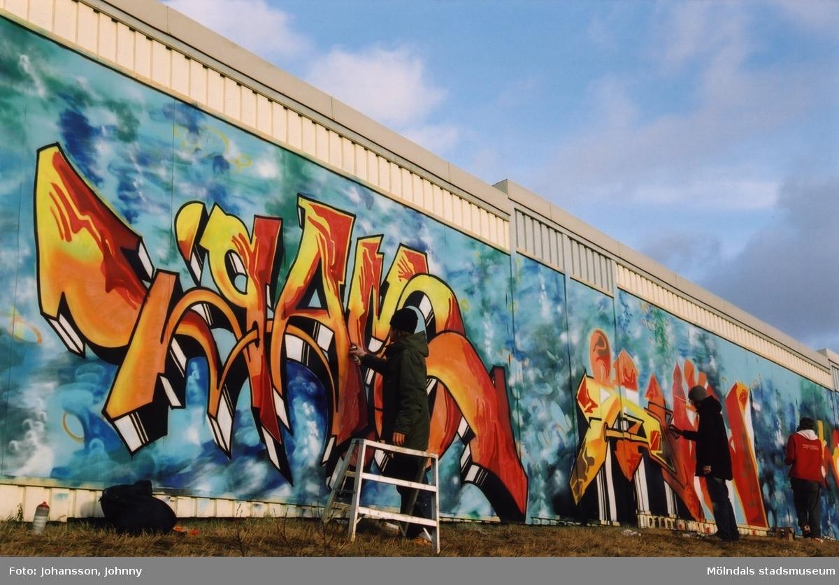 """Graffiti längs Kvarnbygatan i Mölndal, år 2003.  Utställningen """"Alltså finns jag"""" ...en utställning om graffitikultur på Mölndals Museum, Kvarnbygatan 12, Mölndal, pågick från 25 januari till 25 maj 2003. """"Alltså finns jag"""" var ett samarbete mellan Mölndals museum, Vitlycke museum, Bohusläns museum, Västergötlands museum och Konstkonsulenterna i Västra Götalandsregionen."""
