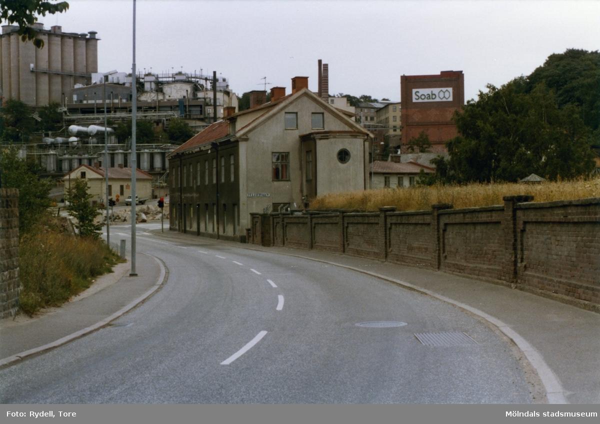 Kvarnbygatan i riktning mot öster. Till höger ses Papyrus mur. I bildens mitt ses nr 4 (idag: Byggnad 213). Lite längre bort på andra sidan gatan ses nr 49 (Götiska förbundets skola). I bakgrunden till vänster ses Soabs industriområde.