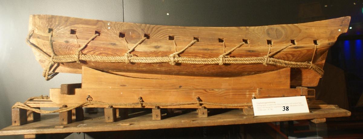 Modell av ett fartyg stående på en upphalningssläde som i sin tur står på en slip. Fartyget består av ett grovt utformat skrov uthugget ur ett trästycke, med kanonportar. Upphalningssläden, som också är grovt utformad, passar inte till skrovet. Både skrov och släde är försett med olika former av linor och trossar för att användas vid upphalning på en slip. Modellen är omålad.   Tolkning: Pedagogisk modell använd för att visa hur linor och trossar skall appliceras vid upphalningen av ett fartyg på en slip för underhåll, reparation eller kanske förvaring. Detta måste ha varit ett mycket komplicerat arbete inte minst p.g.a. fartygets stora vikt. Släden är försedd med lådliknande konstruktioner vid fartygsakter, kanske för att kunna ballastas. Fartyg, släde och slip verkar från början inte höra ihop utan tycks sekundärt sammanförts troligen för att visa en ny funktion som upphalning.  Ingår i modellkammarens inventarium 1804 och 1834. Beskrivningen i 1834 års inventarium är: Upphalningsinrättning med sitt Fartyg Löa (mm): 970Modellens dimensioner (mm):  L 955  B 290   H 340