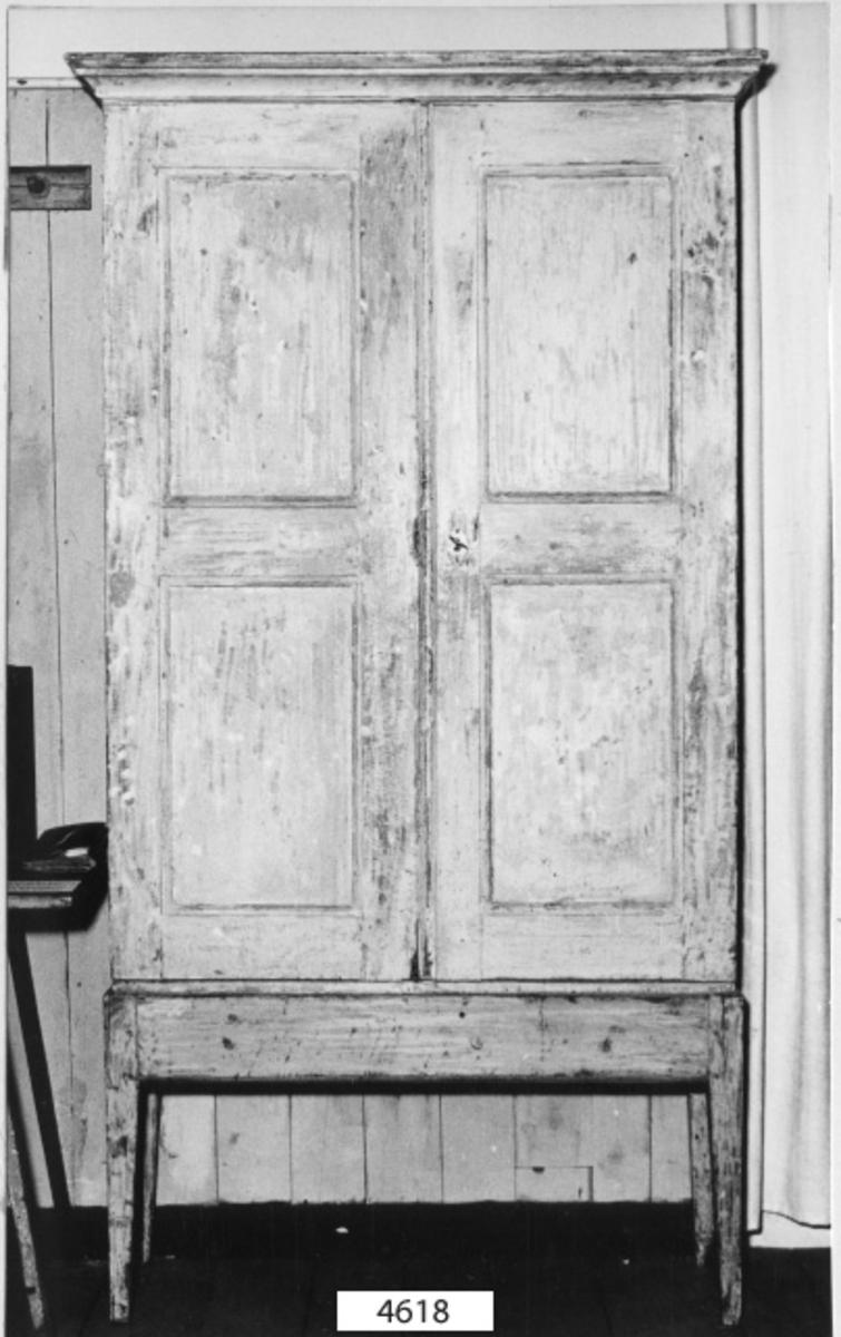 Skåp av trä, i blågrå färg, på ställning av trä med fyra ben. Skåpet försett med två stycken dörrar med haspar och fast lås och nyckel av järn. Invändigt inredning med hyllor och fack.
