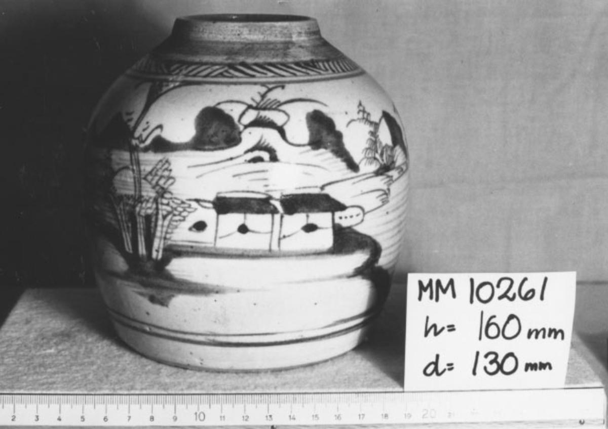 Krus, ingefärs-, kinesiskt. Cylinderformat, utbuktat, avsmalnat upptill med kort hals. Överdraget med glasyr. Dekorerat i grönt med träd, hus, segelbåt och en man m.m.
