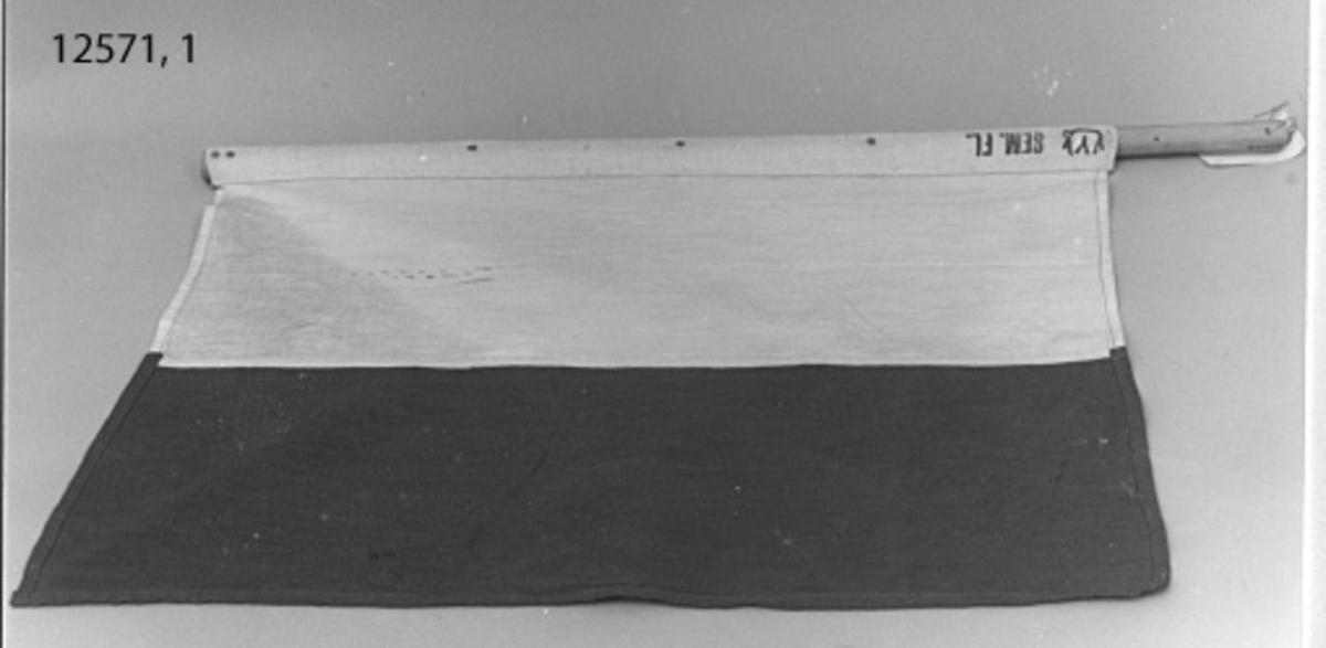 Semafor-flagga. Vit och röd i stående fält. Fastsatt på rund käpp. Märknng: (tre mindre kronor) SEM. FL.