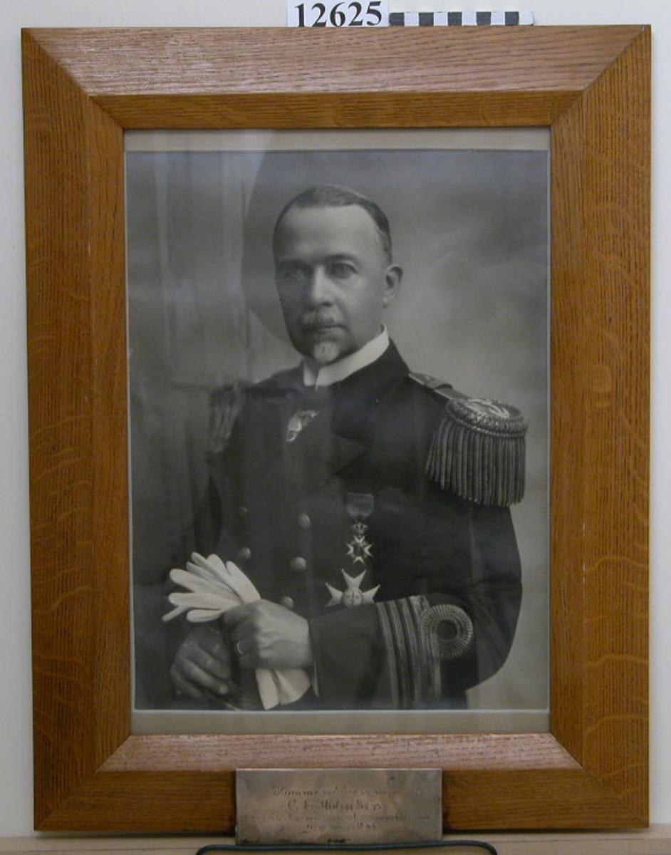 Personfotografi inom glas och ram av ek. Text på namnplåt av försilvrad mässing: Kommendören m.m. C.E. Holmberg Chef för Underofficers- och sjömanskårerna 1/7 1927 - 30/9 1933. Neg.nr 4936-4947.