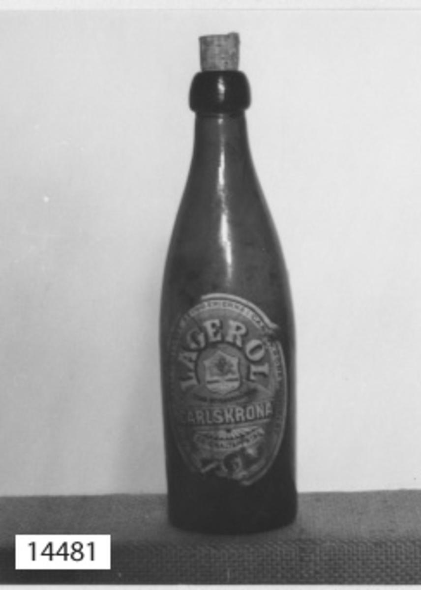 """Flaska öl- Tillverkad av brunt glas. Märkt i botten: VIIII 1900. Märkt på sidan: *L* 1/3 LIT. Försedd med en oval etikett med text: Aktiebolaget förenade bryggerierna i Carlskrona och Lyckeby. LAGERÖL. Carlskrona. Originaltappning. På etiketten fabriksmärke bestående av en sköld med en ek och därunder """"Fabriksmärke"""". Under skölden: Tyska bryggerigården. Försedd med kork märkt: T.B.G. Carlskrona"""