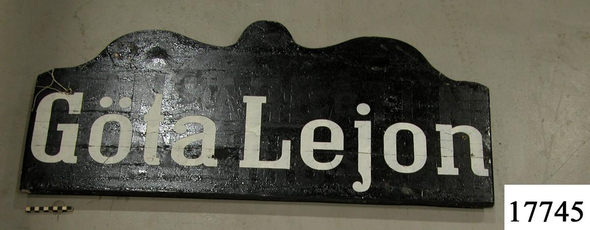 """Rektangulär skylt, ovansidan sågad i tre bågar, svartmålad. Vit schablonmålad text: """" Göta Lejon """", svartmålad baksida."""
