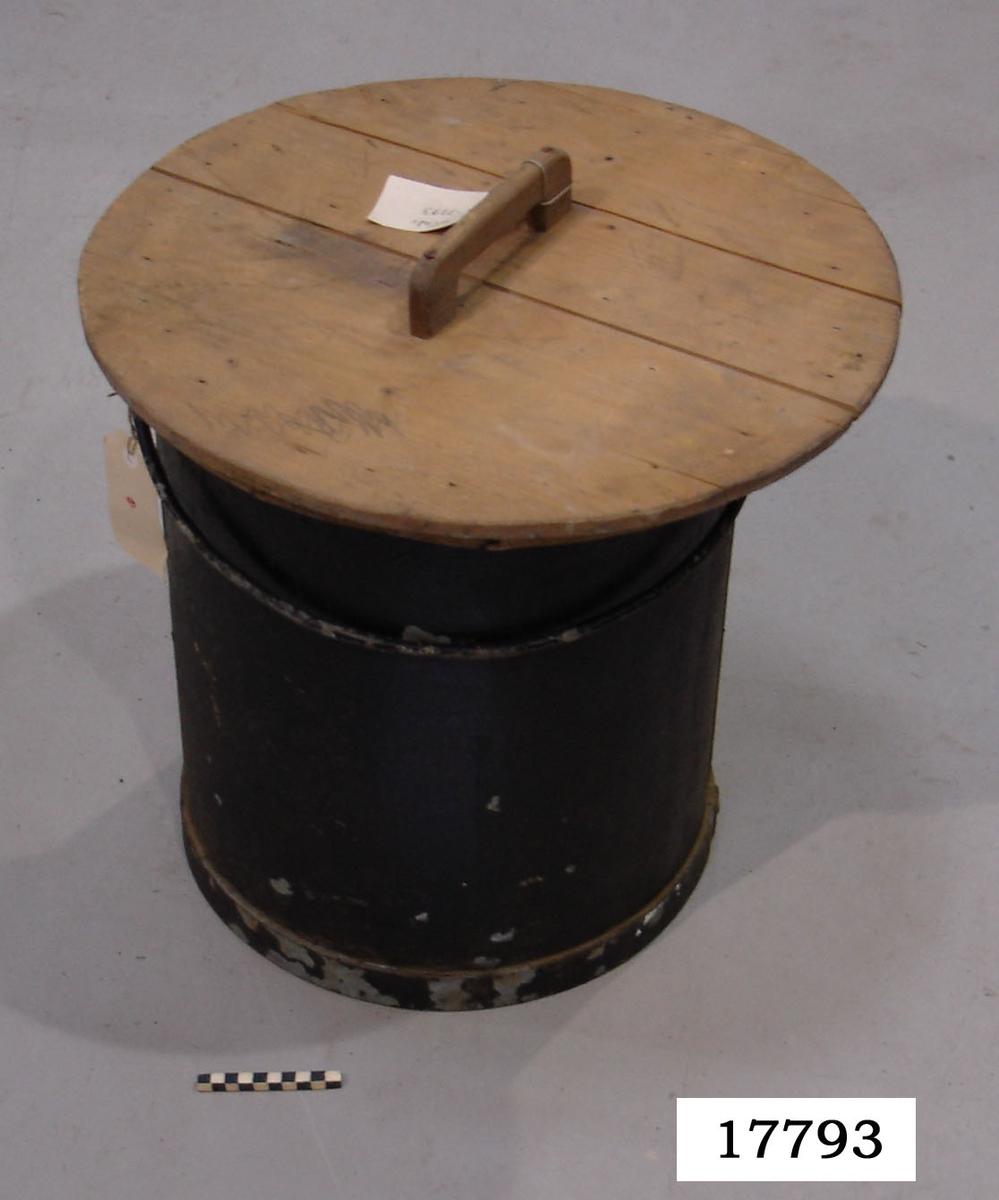 """Åmbar av svartmålad järnplåt?,  Rullad överkant samt  handtag i form av en bygel fastnitad i pytsen, järnband nitat till botten. I botten med svart, bokstäverna """"C.S."""", gråmålad botten. Till ämbaret hör ett lock, tillverkat av sammanfogade träbitar, med ett bygelhandtag på mitten. Locket är förmodligen av sekundär  tillverkning och hör ej ursprungligen samman med ämbaret."""