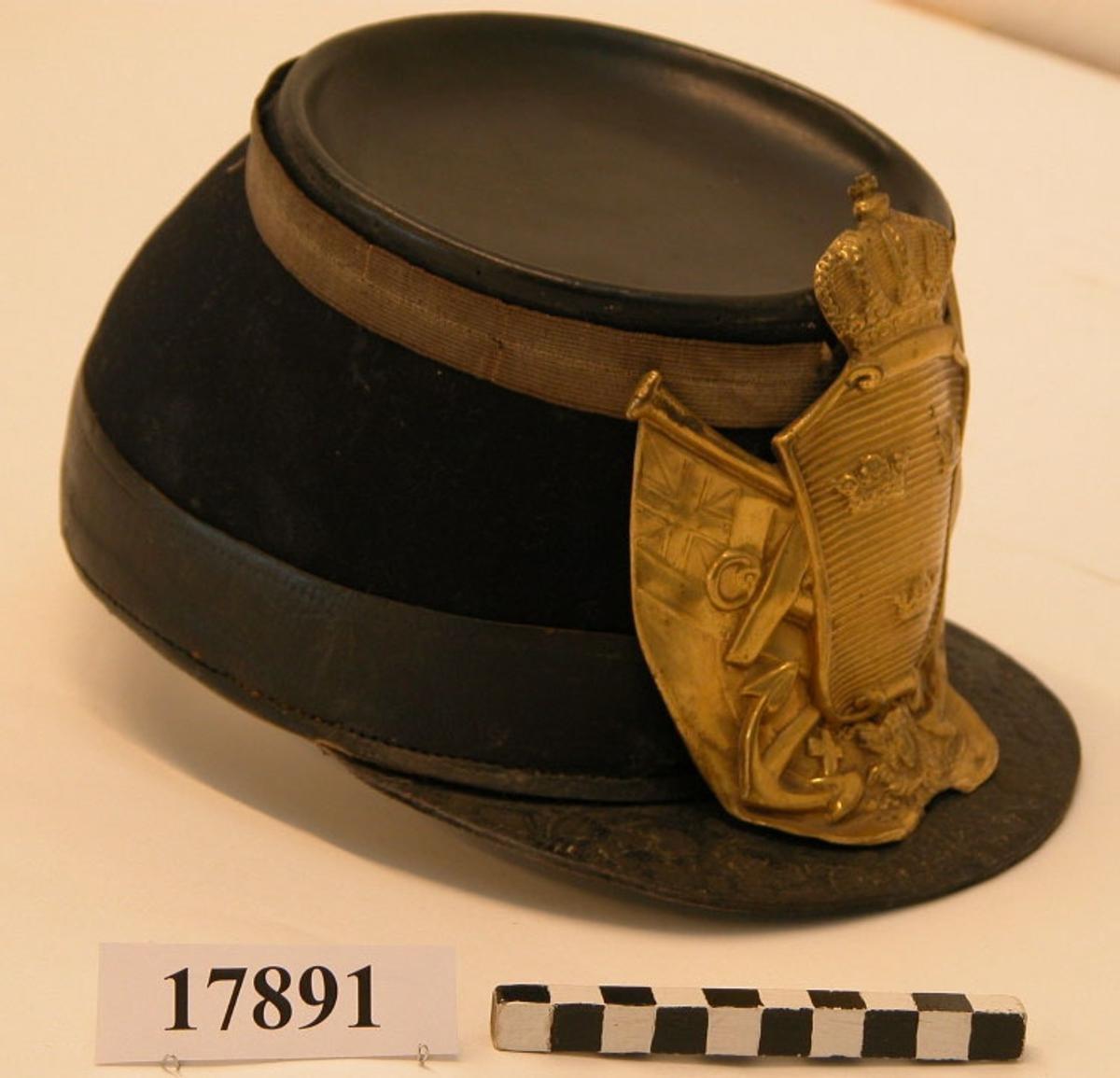 Käppi av läder, utvändigt klädd med mörkblått ylletyg. Svart läderband runt nederkanten (bredd: 35 mm) vävt guldband bestående av två sammansydda band (bredd:17)  runt ovankanten. Käppins ovandel av svart läder. Skärmen av svart läder, bredd: 45 mm. Paradplåt av mässing, höjd:135 mm, bredd: 125 mm, motivet utgöres av lilla riksvapnet i mitten, tre kronor på refflad krönt sköld. Bakom två korslagda stockankare, nederst skymtar en bit av serafimerordens kedja, vid sidorna omgiven av två unionsflaggor. Invändigt klädd med läder samt försedd med rem.
