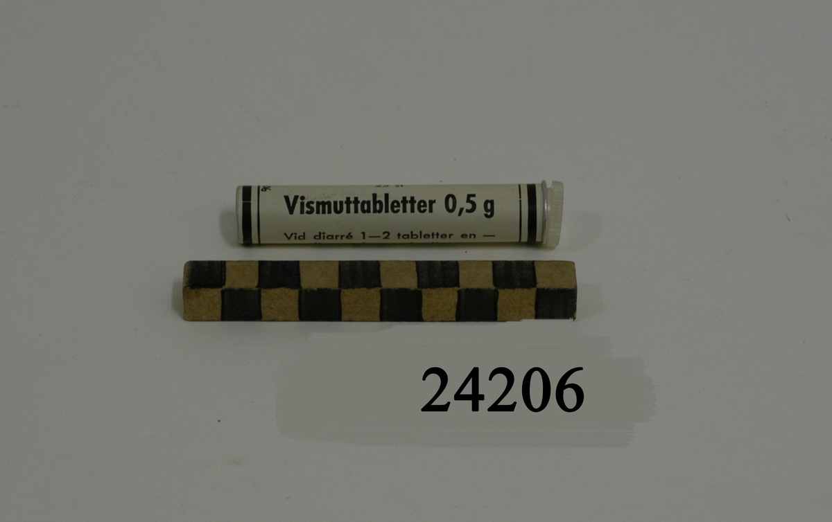 """Smalt vitt rör av metall med skruvkork av plast. Svart text: """"25 st Vismuttabletter 0,5 g. Vid diarré 1 - 2 tabletter en - flera gånger om dagen. MILITÄRAPOTEKET STOCKHOLM""""."""