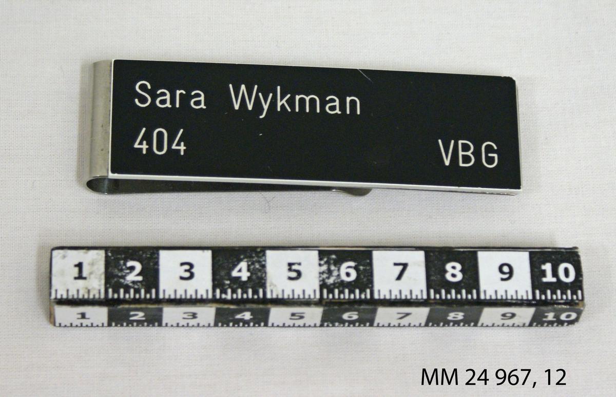 """Namnbricka av stål. Rektangulär platta med clips. På plattan en svart bricka med tryckt text i vitt: """"Sara Wykman 404 VBG"""" (Visborg). Kronstämpel på baksidan."""