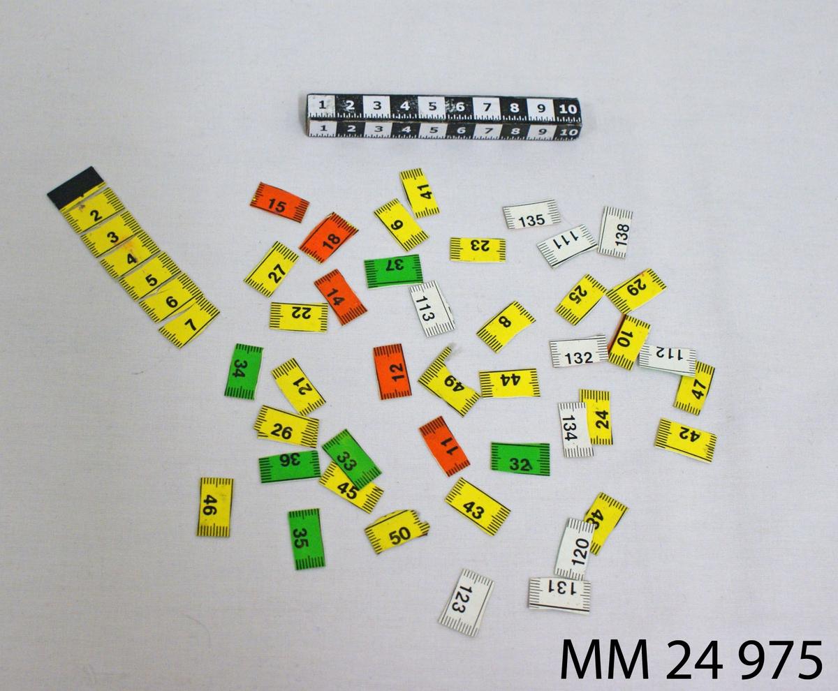 Måttband av plast, sönderklippt i 50 stycken centimeterstora delar. Änddelens kant är försedd med metallplatta. Ena sidan av måttbandet är vit med svart markering, andra sidan är gul, grön eller orange med svart markering.