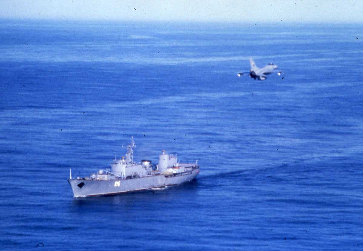 Russisk fartøy av Ugra - klassen med nr. 915. En F-16 passerer over båten.