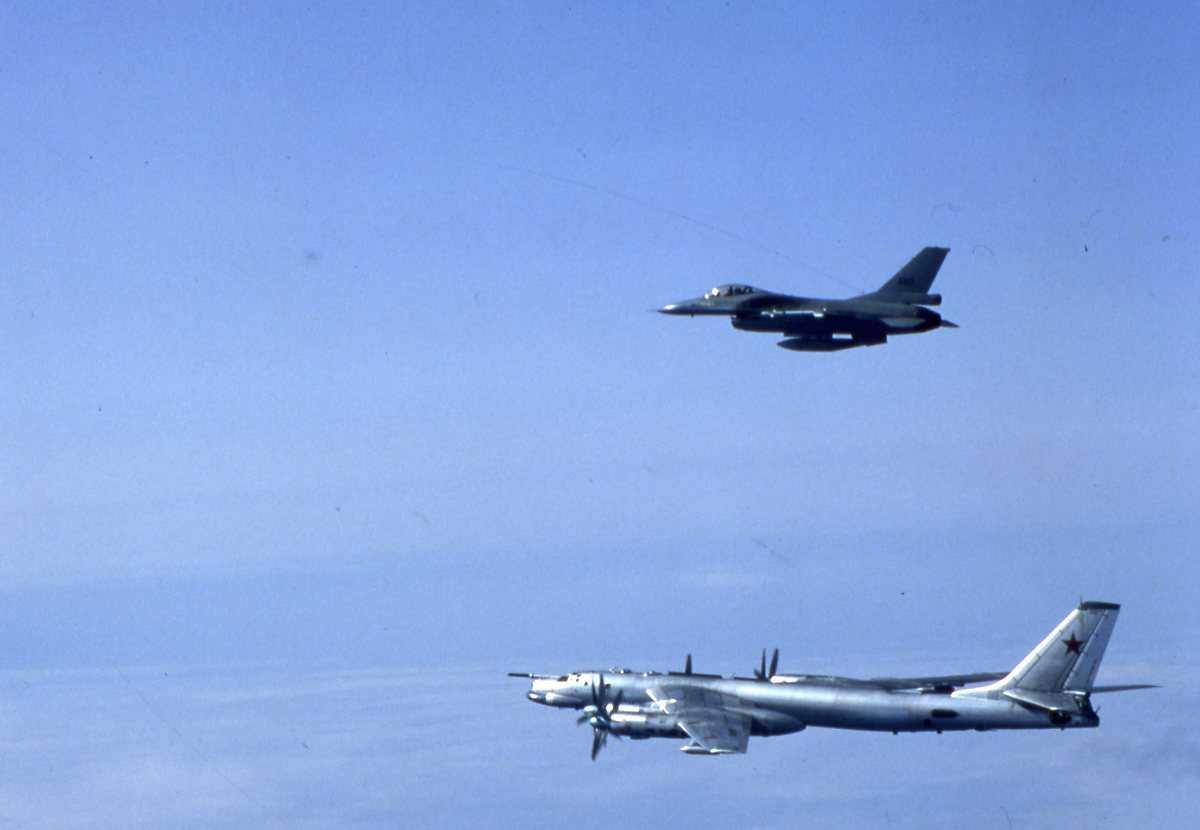 Russisk fly av typen Bear C. Over sees en norsk F-16 med nr. 660.