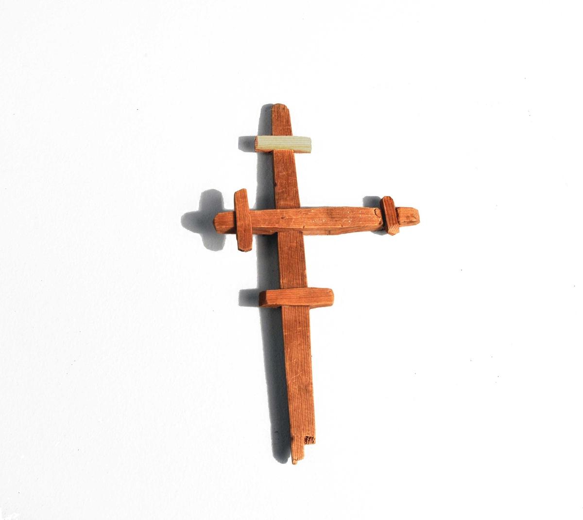 1 Kors av træ.  Kors av furutræ fundet liggende paa en likkiste under gulvet i midskibet, hvor orgelprospektet nu er reist. Korstet har tre tverarmer. Dette kors er utvivlsomt stukket under kirkegulvet i en eller anden overtroisk hensigt. Længde 17,6 cm, midterste tverarms længde 9,5 cm.  Ovennevnte gjenstander (12036 - 51) fundet ved min undersökelse av likkjelderen i Aurlands Kirke og gave fra Aurland Sognestyre.