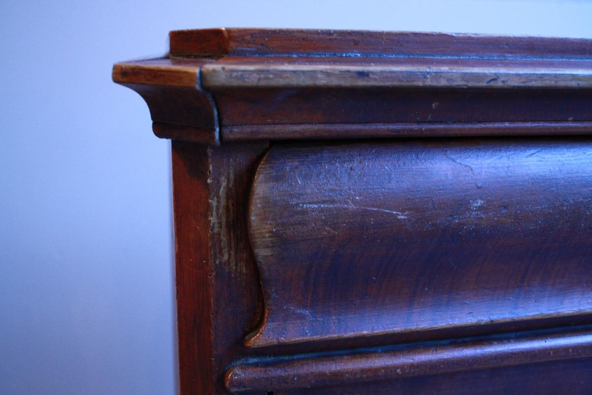 Komode med fire skuffer med barokk stil. Nederste og øvste lås er øydelagt, øvste lås er reparert igjen. Kommoden er beisa. Godt brukt.