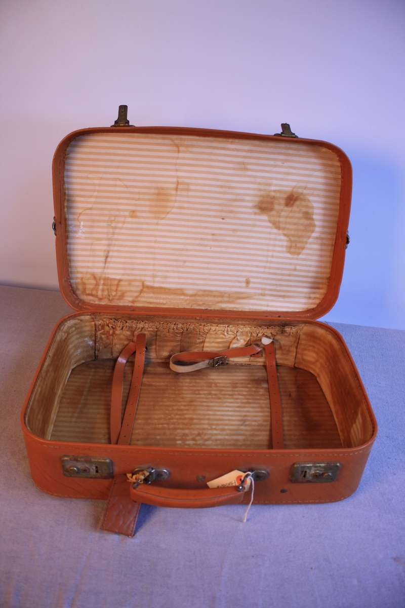 Koffert med avrunda hjørne. To låsar på kvar side av handtaket framme. Skinnreimar inn kista til å feste med. Låg på loftet i Ausevika.
