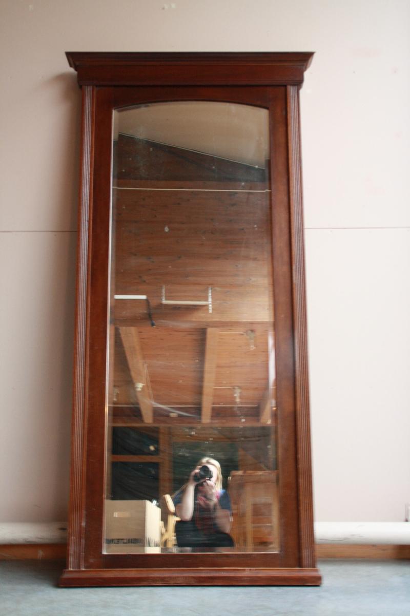 Heilfigurspeil i emperistil. Det følger med ein benk som spegelen har stått på.
